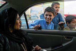 Ravis, des gamins courent le long de la voiture dans une rue de Kaboul.