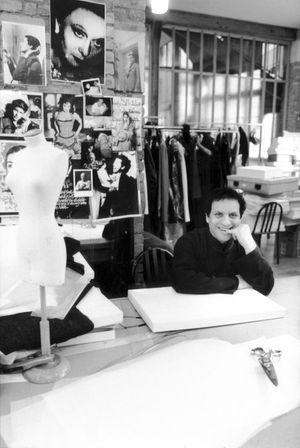 Azzedine Alaïa assis à sa table de travail dans son atelier de couture, en 1998.