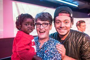 Kev Adams en compagnie d'une petite fille opérée grâce à l'association, dans les bras de sa famille d'accueil.