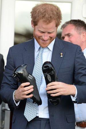 Le prince Harry fort réjoui de son cadeau, des chaussures de rugby à son nom