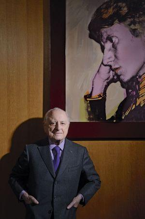 Le 12 décembre dernier, dans son bureau de la Fondation Pierre Bergé-Yves Saint Laurent, devant le portrait du couturier signé Andy Warhol.