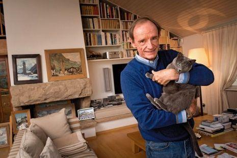 Avec le chat Kalina, dans son salon. Sur la cheminée, des peintures de villages montagnards signées Lucien Poignant et Etienne Bovier-Lapierre.