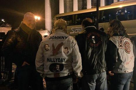 Quatre fans de Johnny Hallyday montrent leur blouson.