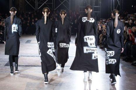 Des messages inscrits comme des graffs sur le dos de longs manteaux noirs