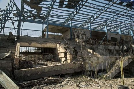 Des soldats américains «embarqués» aux côtés des FDS inspectent les ruines de la tribune après les bombardements de l'US Air Force.
