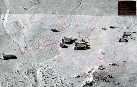 Image d'archive d'une opération de reconnaissance. Bâtiments, types de véhicules et même les combattants sont visibles.