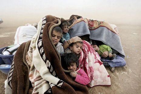 Le mercredi 24septembre, ces Syriens tentent de se protéger d'une tempête de sable au poste-frontière de Yumurtalik, qui mène à la Turquie.