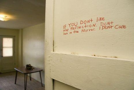 """Sur un mur de son appartement de Montréal, on peut lire: """"Si vous n'aimez pas le reflet dans le miroir, ne regardez pas dans le miroir. Je m'en moque"""""""