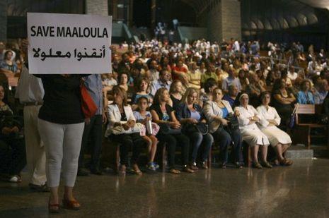 """En septembre dernier, une Syrienne tient une affiche """"Sauvez Maaloula"""", lors d'un rassemblement de chrétiens maronites au Liban."""