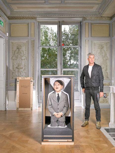 Maurizio Cattelan refuse de se faire photographier à côté de ses oeuvres. Il pose ici derrière la caisse de sa sculpture « Him », figurant Hitler tel un petit garçon sage et pieux.