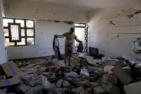 Un soldat irakien découvre des uniformes de militants de Daech dans un appartement dévasté.