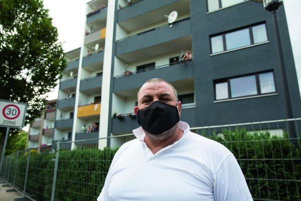 Un ouvrier roumain devant les immeubles de Verl, isolés par des clôtures. Y résident la plupart des employés de Tönnies.