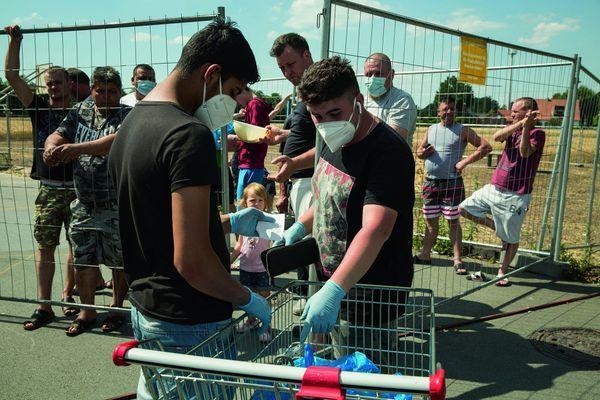 Derrière la clôture, un commerçant distribue les commandes des familles en quarantaine : cigarettes, alcools, douceurs.