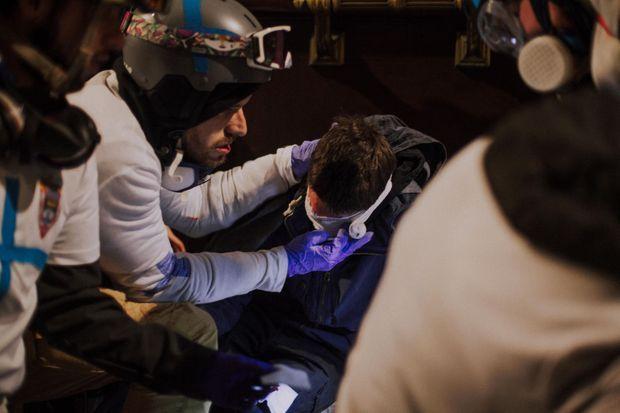 Un passant de 23 ans a reçu un tir de LBD dans l'œil. Le médecin de l'équipe lui octroie les premiers secours.