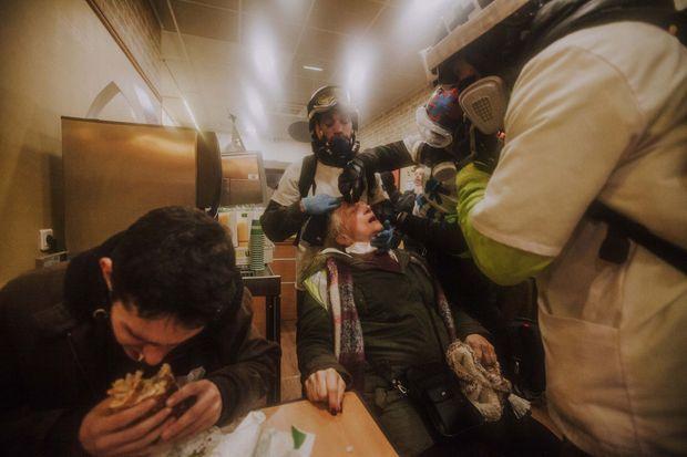 Les street medics soignent une grand-mère au milieu d'un fast-food bordelais. Impassibles, des clients mangent leur sandwich.