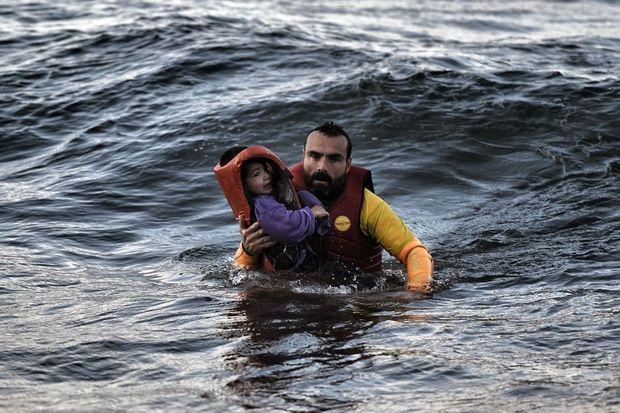 Sur l'île de Lesbos, le 2 novembre: un garde-côte espagnol amène un petit réfugié sur la rive.