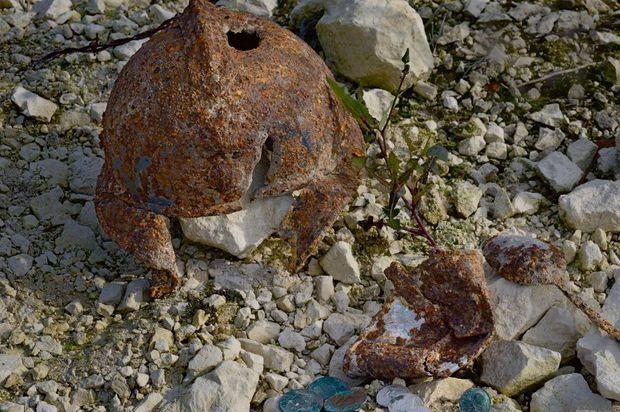 Les objets retrouvés le 16 mai 2012 sur la dépouille d'Arthur Leguay : son casque percé d'un éclat d'obus, sa plaque d'identité et ses deux médailles religieuses au premier plan, quelques pièces de monnaie, son gobelet écrasé et une cuillère (à dr.).