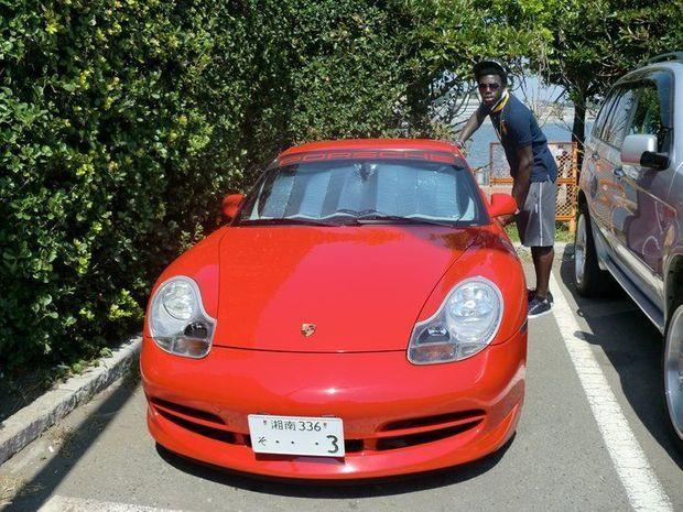 Ufot Ekong à côté d'une Porsche.