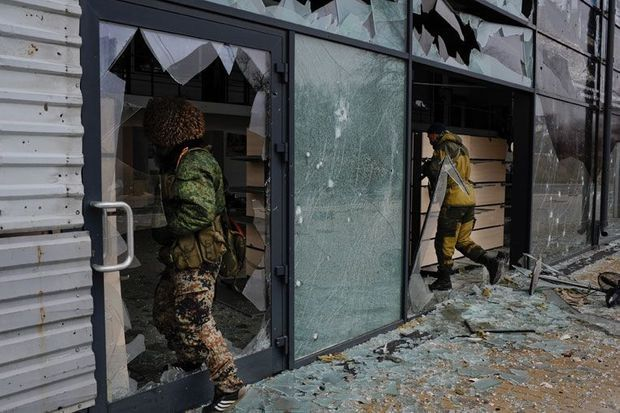 """Des membres du bataillon Vostok-""""Unite Youg"""" pénètrent un bâtiment sur la route principale qui mène a l'aéroport de Donetsk, à quelques centaines de mètres de violents combats entre forces ukrainiennes et pro-russes."""