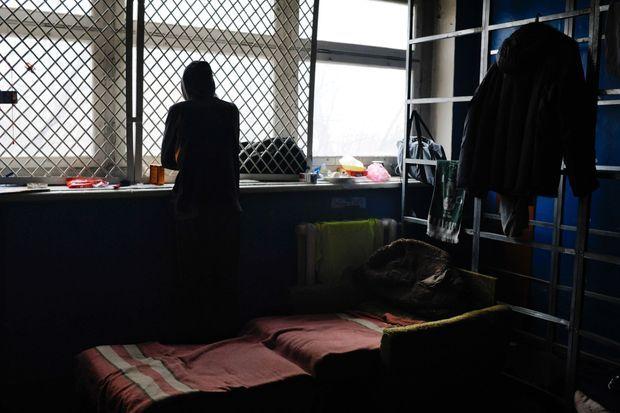 Un prisonnier regarde par la fenêtre de sa cellule.