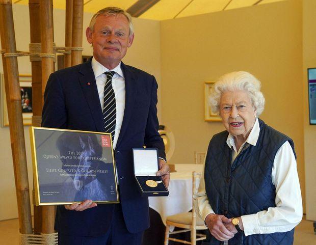 La reine Elizabeth II remet le «British Horse Society Queen's Award for Equestrianism» à l'acteur Martin Clunes à Windsor, le 2 juillet 2021