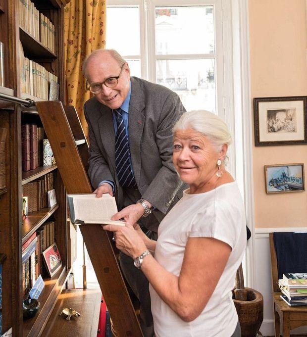 Alain et Nicole Pompidou dans leur bibliothèque avec un exemplaire dédicacé des « Mémoires » du général de Gaulle.