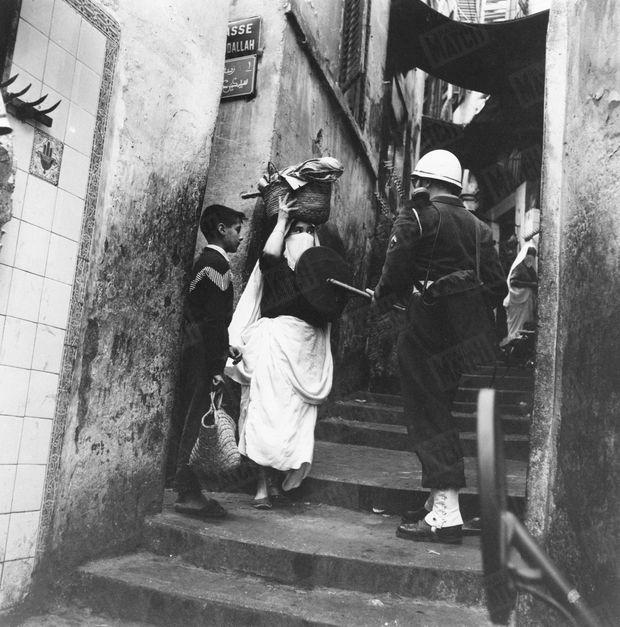 Tous suspects dans la Casbah : Un soldat français passe cette femme au détecteur de métaux dans une ruelle de la casbah en janvier 1957. La bataille d'Alger vient de débuter. Elle est remportée dix mois plus tard par les paras du général Massu, qui réussissent à asphyxier le FLN. Mais la victoire a un prix: les centaines d'attentats des indépendantistes, et une controverse durable sur les méthodes musclées de Massu.