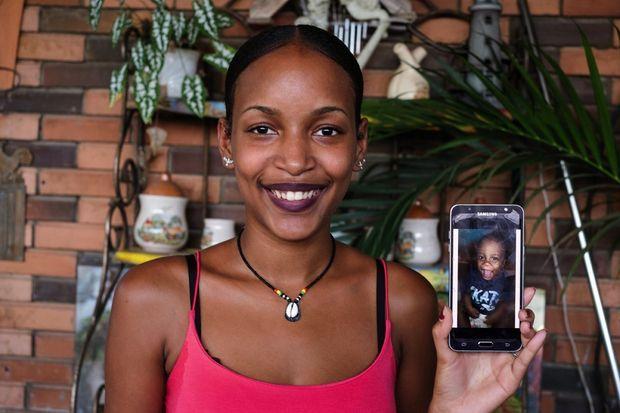 Aline, 16 ans, avec une photo de son fils de 11 mois sur son portable. La journée, c'est le père qui le garde.