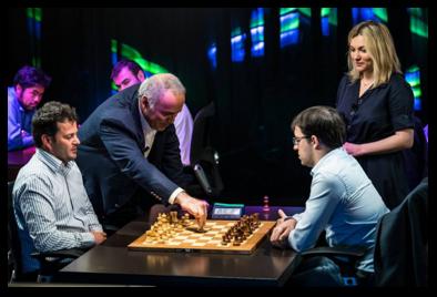 Sous l'œil amusé d'Almira Skripchenko, Garry Kasparov pousse le premier pion d'une partie opposant les deux champions français : Etienne Bacrot (à g.) et Maxime Vachier-Lagrave (à dte).
