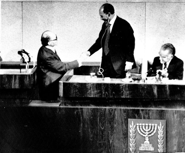 Le président égyptien Anouar el-Sadate, debout, serre la main du Premier ministre israélien Menahem Begin, après son discours devant la Knesset, le Parlement israélien, le 19 novembre 1977.