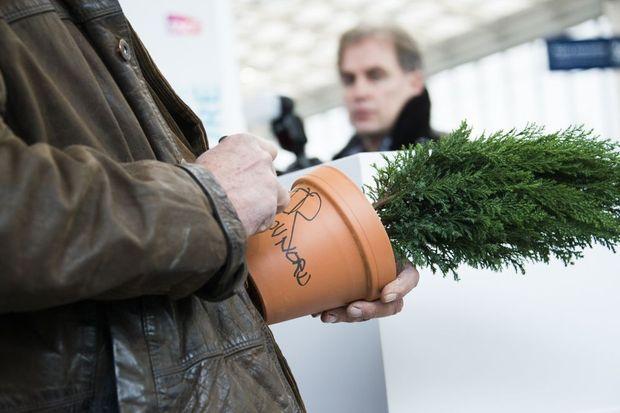 Philippe Pastor dédicace le pot d'un jeune arbuste destiné à Madagascar.