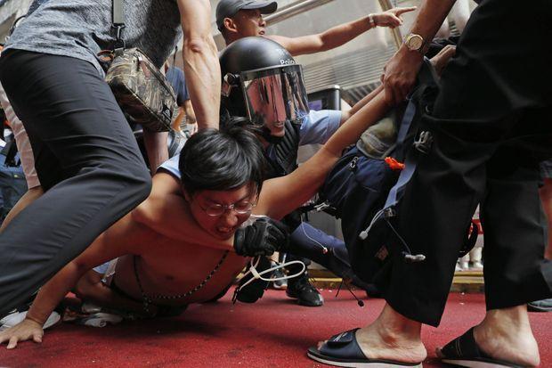 Arrestation musclée d'un contestataire à Amoy Plaza. Depuis le début du mouvement, des centaines de manifestants ont été incarcérés par les forces de l'ordre, dont 44 jugés pour « émeute ». Ils risquent jusqu'à dix ans de prison.
