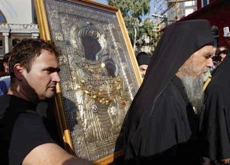 Les moines et visiteurs pénètrent dans l'église où la messe est célébrée debout.