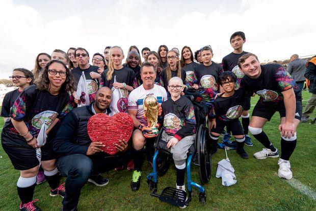 Autour de Pascal Olmeta tenant le trophée de 1998, les enfants soutenus par l'association et, sur le fauteuil, Maxence atteint d'un ostéosarcome.