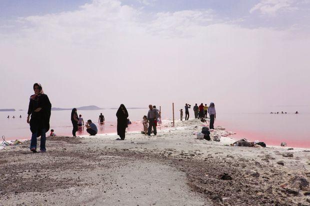 Autour de ses eaux rosies par le sel et les algues proliférantes, quelques Iraniens viennent faire trempette ou jouent à flotter sur la mer Morte.