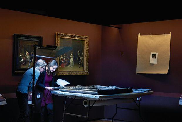 Avant l'accrochage. Une restauratrice et la responsable du convoiement font le « constat d'état » du dernier tableau arrivé. Derrière elles, « La visite », de Gerard Ter Borch (1660).