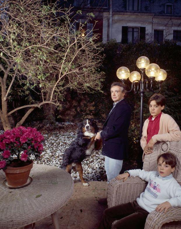 Avec ses fils, Romain, 13 ans, Davy, 9 ans, et leur chien César dans le jardin de son hôtel particulier à Paris, en 1987.