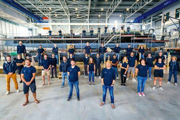 Avec toute l'équipe de sa société, MerConcept, sur son chantier de construction de bateaux. Le nouveau trimaran Ultime y est en cours d'assemblage.