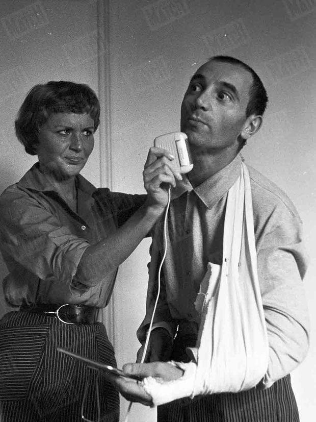 La première photo de Charles Aznavour publiée dans Match, numéro 392, daté du 13 octobre 1956. Le chanteur a les deux bras plâtrés après un accident de voiture, et son épouse Evelyne Plessis l'aide à se raser avant un concert.