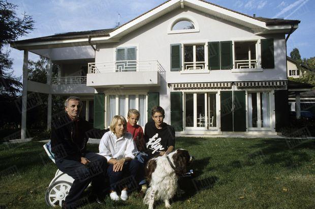 Charles Aznavour, Ulla, leurs deux fils Micha (15 ans) et Nicolaï (10 ans) et Twiggy, un English Springer Spaniel devant la maison de Cologny, en Suisse, le 25 septembre 1987.