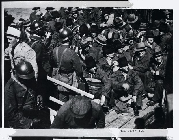 Des forçats attendant sur un quai de l'Île de Ré, avant de monter à bord du navire à destination des bagnes de la Guyane (non datée).