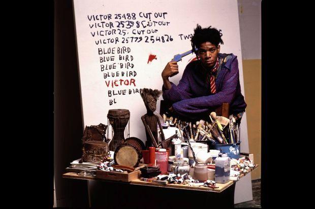 En 1987, dans son atelier de New York. Il se colle un pistolet factice sur la tempe devant une poupée vaudoue à son effigie.