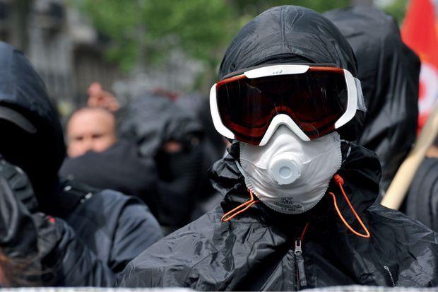 La tenue de combat : capuche, T-shirt noué autour de la tête, coupe-vent noir, lunettes de ski ou de piscine, masque à gaz.
