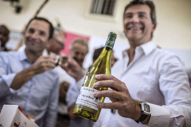 """Benoît Hamon et Arnaud Montebourg dégustent une bouteille de """"cuvée du redressement"""" le 24 août 2014."""