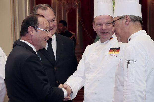 Le 24 juillet 2012, François Hollande serre la main de Ulrich Kerz et Bernard Vaussion. Kerz est le chef cuisinier de la chancellière Angela Merkel.