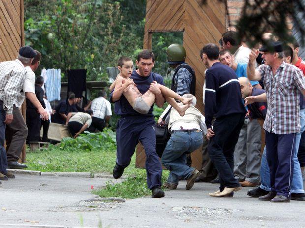 """""""Dernières images d'espoir : après la forte explosion, des proches qui attendent depuis deux jours à la porte de l'école parviennent à évacuer des petits otages. Pourtant, les corps des enfants, blessés, à moitié nus, font déjà pressentir le drame."""" - Paris Match n°2886, 9 septembre 2004"""