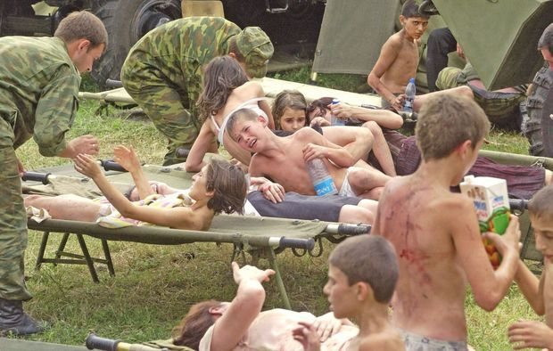"""""""Des jeunes otages essaient de se réconforter mutuellement. La chaleur était telle à l'intérieur de l'école assiégée qu'ils ont été forcés de se dévêtir. Assoiffés, certains enfants ont dû boire leur propre urine."""" - Paris Match n°2886, 9 septembre 2004"""