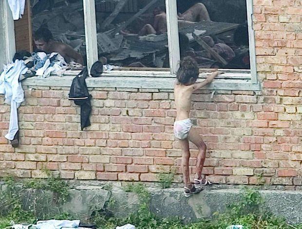 """""""Devant le gymnase dévasté par la double explosion, une jeune otage se redresse péniblement. Dans le bâtiment, les survivants sont hagards."""" - Paris Match n°2886, 9 septembre 2004"""