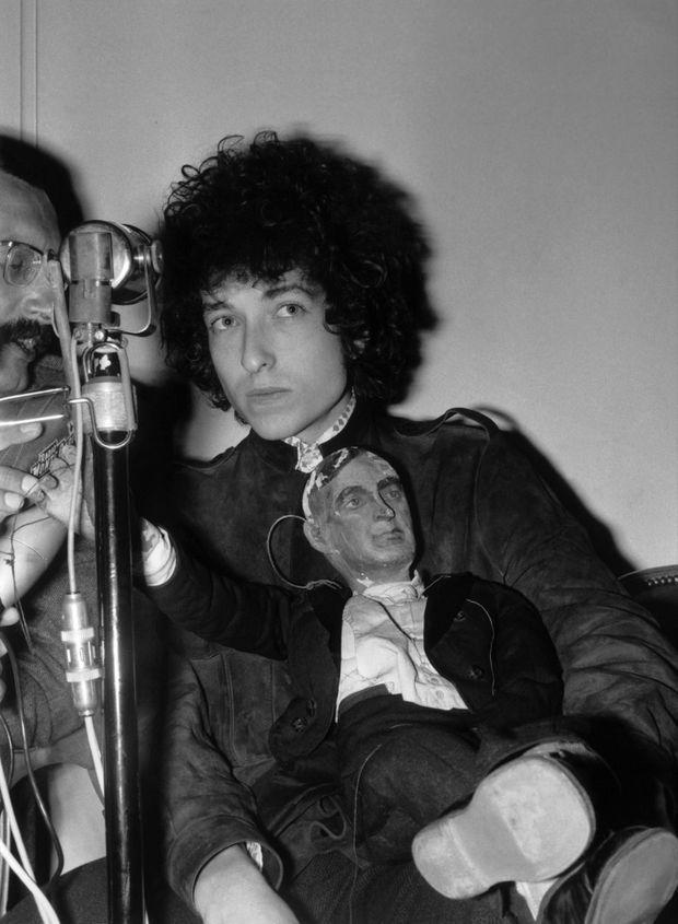 Bob Dylan, accompagné de sa poupée en bois, donne une conférence de presse à l'hôtel George V à Paris, avant son concert à l'Olympia en mai 1966.