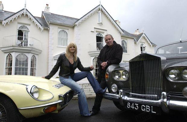 « Bonnie et son mari devant leur maison de Swansea, au pays de Galles. Robert est accoudé à la Rolls Royce qu'il a offerte à sa femme. Bonnie est assise sur une Jaguar, un cadeau fait en retour à Robert. » - Paris Match n°2873, 10 juin 2004